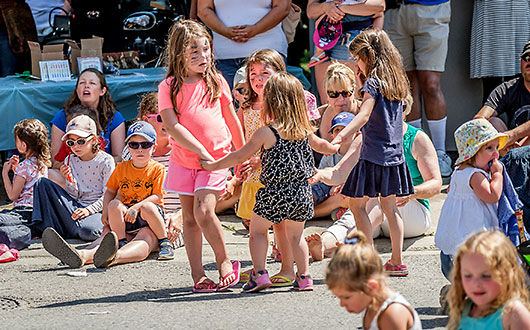 families with children sitting on the street, little girls dancing