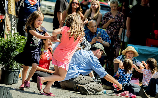 children dancing, family sitting on the ground, playing