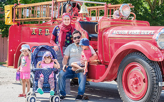 family with three kids posing in front of old red fire truck