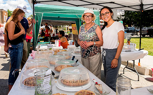 two women, vendors with pies, smiling