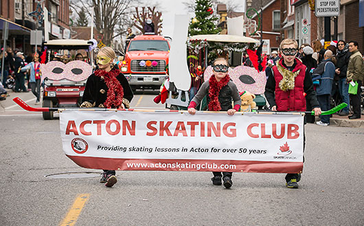 children in masks holding Acton Skating Club banner in parade
