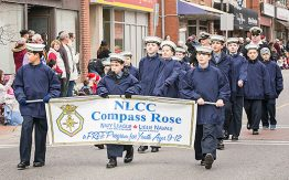 children in blue jackets and white caps holding Navy League banner in parade