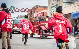 old red fire truck in the parade, boys in red jerseys running