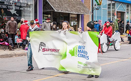 children holding Superior Glove banner in Santa Claus parade