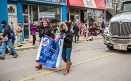 two girls walking in the parade holding a banner of MacKenzie Smith Bennett school