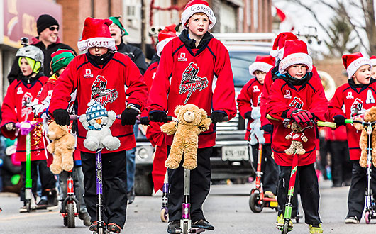 sports tam of children in red jerseys riding scooters with teddy bears on handlebars