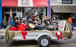 youth band playing instruments, sitting on an open trailer in Santa Claus parade