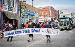 "two kids and one adult holding ""Robert Little Public School"" banner in Santa Claus parade"