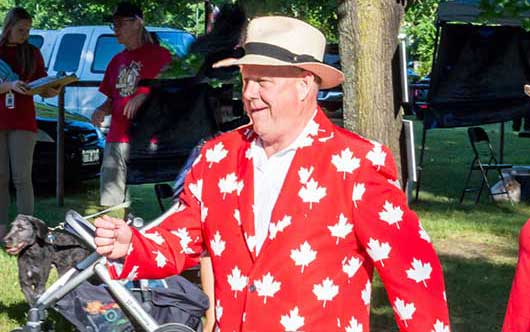 man dressed in red and white suite made of maple leafs