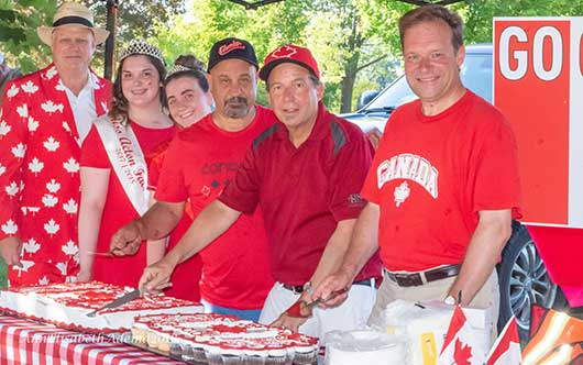 counsellors, mayor, MP Arnott and two girls cutting Canada Day cake