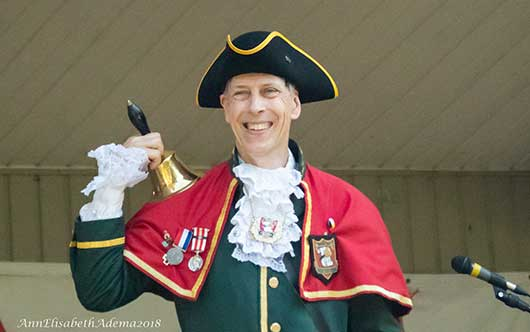 man in Master of Ceremonies costume, smiling, holding a bell