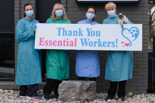 """People standing in line holding """"Thank You Essential Workers"""" sign."""