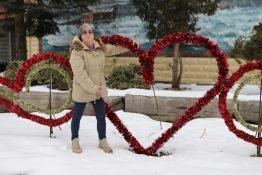 Lynda Brasz standing with Valentine's Heart Decoration in the parkette.